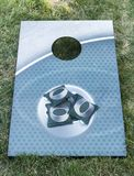Corn hole game with bean bags on the board. An metal aqua colored corn hole board is on green grass with green bean bags on it royalty free stock image