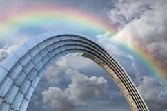 A metal arc and rainbow. A metal arc on the background of the cloudy sky with rainbow Stock Images