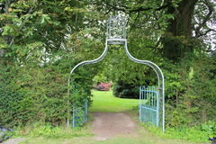 Metal arch in the garden. Summer garden.  The metal arch is an entrance to  a garden Royalty Free Stock Photography
