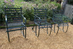 Metal armchairs on a gravel path in a garden. Garden furniture of metal chairs on a gravel garden path Royalty Free Stock Image