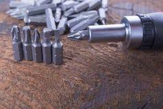 Metal as cabeças da chave de fenda, bocados com a chave de fenda na madeira fotos de stock
