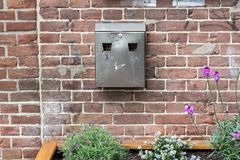 Metal ashtray on a brick stone wall with some plants and flowers. Metal ashtray on a brick stone wall from an old building with some plants and flowers in the Stock Photo