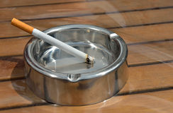Metal ashtray with a cigarette Stock Photo