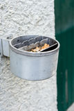 Metal ashtray on a wall full with cigarette old retro style not cleaned Royalty Free Stock Photography