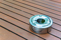 Metal ashtray on wooden table Royalty Free Stock Photo