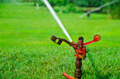 A metal automatic water sprinkler in the field Royalty Free Stock Images