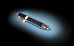 Metal ballpoint pen on a dark background. Metal pen on a white background, focused on the tip (ball point Royalty Free Stock Photography