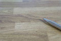 Metal ballpoint pen lay in wooden table. Room for text,top view royalty free stock photos