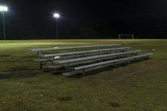 Metal a bancada em um campo de futebol vazio na noite Imagem de Stock Royalty Free