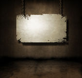 Metal banner hanging. In a dark grungy room Royalty Free Stock Photos