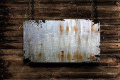 Metal banner hanging. A metal banner held with chains on a grungy wood background - room for copy on the banner Stock Images