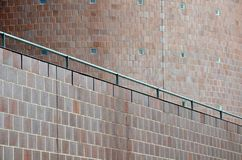 Metal bannister alongside curved facade of modern building. Metal railing on top of a wall alongside curved brick facade of modern building stock photography
