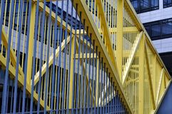 Metal bannister at footbridge in business district. Railing, partly painted yellow at footbridge in a business district of a city royalty free stock image