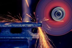 Metal bar being cut with electric grinder with spark flying, selective focus. 