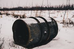 Metal barrel in winter scenery. Old metal barrel on the snow Stock Images