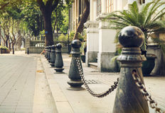 City street sidewalk roadside. Detail of black metal barriers with iron chain on the city street sidewalk by the roadside Stock Photography