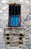 Ancient Window Eze France. Ancient buildings dating back to the time of the Romans in Eze, France are still occupied today. This glassed in window with iron bars Stock Photo