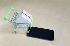 Metal basket with box, mobile phone, concept online store stock image