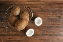 Metal basket with coconuts. On wooden background Stock Image