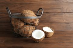 Metal basket with coconuts. On wooden background Royalty Free Stock Image