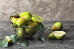 Metal basket and delicious ripe pears. On table Stock Photo