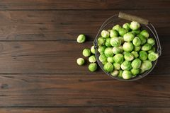 Metal basket with fresh Brussels sprouts on wooden background, top view. Space for text stock image