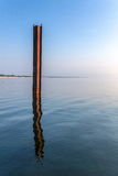 Metal beam sticking out of the water Stock Photography