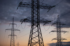 Metal Bearing high voltage power line at sunset Royalty Free Stock Photography
