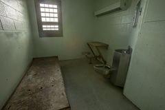 Metal bed inside solitary confinement cell. Interior of solitary confinement cell with metal bed, desk and toilet in old prison Stock Images