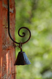 Metal Bell. Rusty metal bell hanging on decorative iron-work scroll Stock Photo