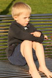 On the metal bench. Small boy is sitting on the bench in the irish sunshine Royalty Free Stock Images