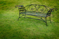 Metal bench on green grass Royalty Free Stock Photography