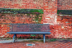 Metal bench and old brick wall in Alba, Italy. Stock Photos