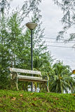 A metal bench and streetlamp in public park Stock Photos