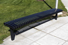 A metal bench under the sun. With green grass in the background Royalty Free Stock Photo