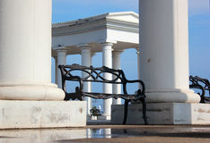 Metal benches in white rotunda in a park Stock Images