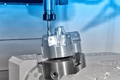 Metal billet in an industrial milling machine. Blue toning. Metal billet is machined on an industrial milling machine.Blue toning stock photography