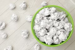 Metal bin and crumpled paper on floor, top view. Space for text stock image