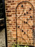 Metal Bird Sculpture Against a Brick Wall. A metallic arch sculpture with small birds set against a brick wall royalty free stock photos