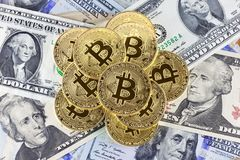 Metal bitcoin coins on dollar bills background. Royalty Free Stock Photography