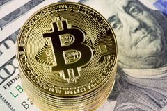 Metal bitcoin coins on one hundred dollar bills background. Stock Photography