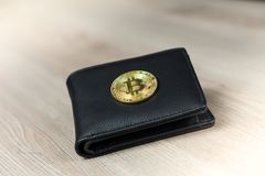 Metal bitcoins in black leather wallet. Bitcoin - modern virtual stock photo