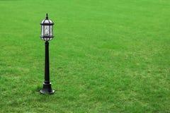 Metal black street lamp on green grass Royalty Free Stock Image