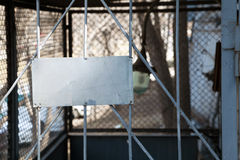 Metal blank sign on the prison type gray bars. Place for text Royalty Free Stock Images