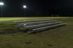 Metal bleachers on an empty soccer field at night Royalty Free Stock Image