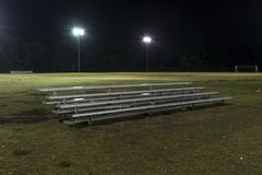 Metal bleachers on an empty soccer field at night Royalty Free Stock Photo