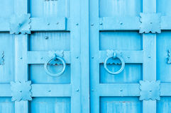 Metal blue aged textured door with rings door handles and metal details in form of stylized flowers. Royalty Free Stock Images
