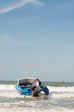 Boats on beach. Metal boat on beach laved by waves Stock Photography