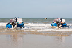 Boats on beach. Two metal boats on beach,laved by waves Royalty Free Stock Images