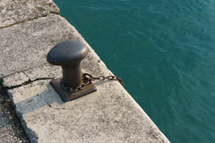 Metal bollard and chain on a quay Royalty Free Stock Photos